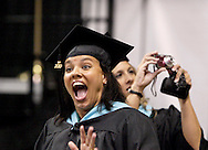 WSU students smale and take pictures as they head for their seats during the processional during Wright State University's 43rd Semiannual Commencement at the Nutter Center, Saturday, June 12, 2010.