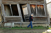 Elsie Eiler walks past an abandoned building that was once a general store slowly decaying in Monowi, Nebraska April 28, 2011. At its peak in the 1930's the town had 150 residents but after the railroad left it began to decline. Now down to a population of just one, Monowi is the only incorporated town, village or city in the United States with just a single resident. The general store closed when World War II started and the owner moved out of town to serve on the draft board.  REUTERS/Rick Wilking (UNITED STATES)