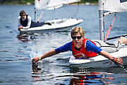 A Laser sailor paddles off the bow of his boat during a postponement due to light wind on the first day of the 2011 Midwest Junior Olympics sailing regatta at Wayzata Yacht Club.