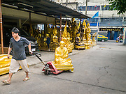 "12 NOVEMBER 2012 - BANGKOK, THAILAND:   A man delivers an unfinished Buddha statue to a workshop on Bamrung Muang Street in Bangkok. Thanon Bamrung Muang (Thanon is Thai for Road or Street) is Bangkok's ""Street of Many Buddhas."" Like many ancient cities, Bangkok was once a city of artisan's neighborhoods and Bamrung Muang Road, near Bangkok's present day city hall, was once the street where all the country's Buddha statues were made. Now they made in factories on the edge of Bangkok, but Bamrung Muang Road is still where the statues are sold. Once an elephant trail, it was one of the first streets paved in Bangkok. It is the largest center of Buddhist supplies in Thailand. Not just statues but also monk's robes, candles, alms bowls, and pre-configured alms baskets are for sale along both sides of the street.    PHOTO BY JACK KURTZ"