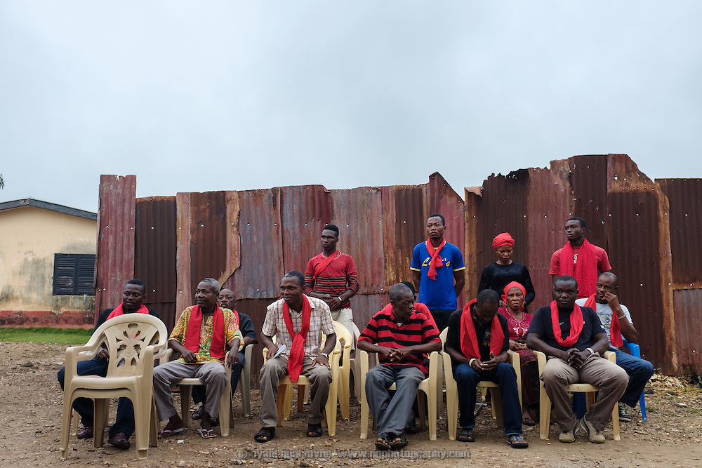 A delegation from a family that had recently lost a mamber at a weekly early morning meeting of the clan to which they belong.  Red signifies that the wearer is in mourning. The clan is an important is an important part of the community's social fabric, and members pay dues to cover administration, funerals and other costs.