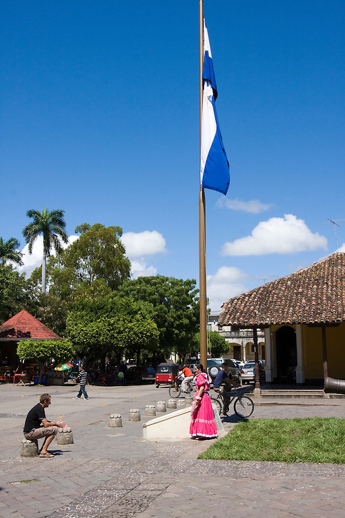 A tour guide dressed in a costume, tells a seated tourist the history of the area while standing under a Nicaraguan flag.
