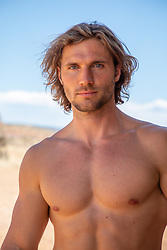 hot shirtless man with long brown hair and blue eyes outdoors