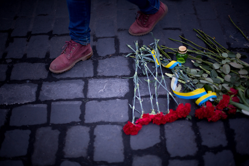 A man walks next to red flowers and ukrainian-colored rubans, lay on the pavement by protesters, on the Independance Square, in Kiev.