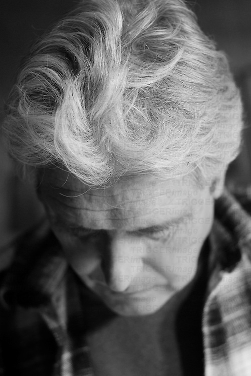 a pensive senior man concentrates while working, a portrait in black and white, suburban albuquerque, new mexico, usa
