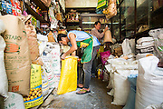 22 JANUARY 2013 - BANGKOK, THAILAND:  A shopkeeper on Chareon Krung Road, in Bangkok's Chinatown, puts out baking supplies.       PHOTO BY JACK KURTZ