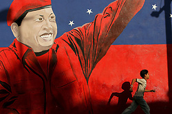 A child runs by a mural of Hugo Chavez that sits right outside of a government complex which houses a subsidized food market as well as two factories, staffed by cooperatives.