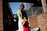 Ntonya Janett, 39, and her son, Noah Findlay, 3, are portrayed in front of their house in BedZED on Thursday, Sep. 6, 2007. BedZED or the Beddington Zero Energy Development, is an environmentally-friendly housing development near Wallington, England in the London Borough of Sutton. It was designed by the architect Bill Dunster who was looking for a more sustainable way of building housing in urban areas in partnership between the BioRegional Development Group and the Peabody Trust. There are 82 houses, 17 apartments and 1,405 square meters of work space were built between 2000. The project was shortlisted for the Stirling Prize in 2003. The project is designed to use only energy from renewable source generated on site. In addition to 777 square meters of solar panels, tree waste is used for heating and electricity. The houses face south to take advantage of solar gain, are triple glazed and have high thermal insulation while most rain water is collected and reused. Appliances are chosen to be water efficient and use recycled water wherever possible. Low impact building materials were selected from renewable or recycled sources and were all originating within a 35 mile radius of the site to minimize the energy required for transportation. Also, refuse collection facilities are designed to support recycling and the site encourage eco-friendly transport: electric and LPG cars have priority over petrol/diesel cars, and electricity is provided by parking spaces appositely built for charging electric cars.