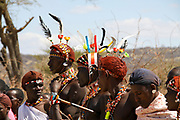 Masai (Also Maasai) Tribesmen an ethnic group of semi-nomadic people. Warriors with traditional headdress made of colourful feathers and ochre hair . Photographed in Maasai Mara, Kenya