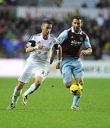 Swansea City's Alvaro Vazquez battles for the ball with West Ham United's Razvan Rat - Photo mandatory by-line: Joe Meredith/JMP - Tel: Mobile: 07966 386802 27/10/2013 - SPORT - FOOTBALL - Liberty Stadium - Swansea - Swansea City v West Ham United - Barclays Premier League