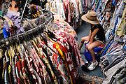 "Bored child (8 years old) wearing Akubra hat sitting amongst Hawaiian shirts (aka ""aloha shirts"") for sale at Bailey's Antiques and Aloha Shirts store in Honolulu, Hawaii"