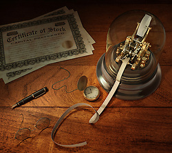 Vintage stock brokerage desk with ticker tape machine, simulated shares of stock, candlestick telephone, fountain pen, pocket watch and library desk lamp