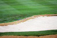 2006:  Stock Golf course detail, graphic, product, grass, sky, ball, fans, gallery, people, color.  Sand bunker with rake.