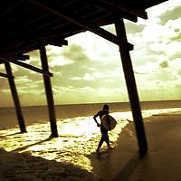 A figure holding a surf walking under a timber pier