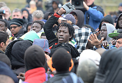 "Tempers flair up among a large crowd of migrants as they line-up at a processing centre in ""the jungle"" near Calais, northern France, as the mass exodus from the migrant camp begins."