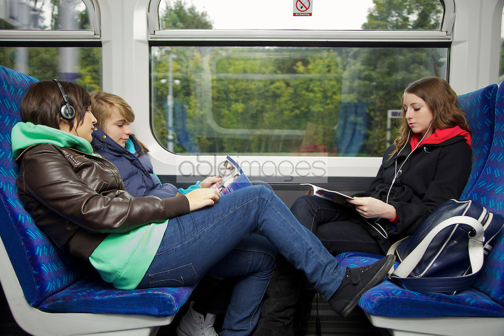 Teenage Girls Sitting on Train Reading and Listening to Music