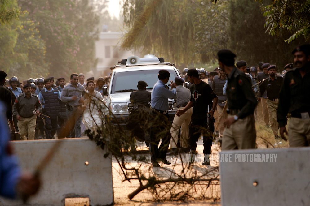 ISLAMABAD, PAKISTAN - NOVEMBER 09: Police attempt to stop a 4x4 carrying former Pakistani Prime Minister, Benazir Bhutto, as her driver breaks through police lines after she was placed under house arrest on November 9, 2007 in Islamabad, Pakistan. Bhutto was placed under house arrest to prevent her from participating in a planned rally by her political party, the Pakistan People's Party (PPP). Bhutto broke through police lines outside her home to address the media and condemn the move by President Musharraf  and urge him to stick to his commitments of removing his uniform and holding elections. The president declared emergency rule on Saturday, just days before the Supreme Court was to decide on the legitimacy of Musharraf's presidency. (Photo by Warrick Page)