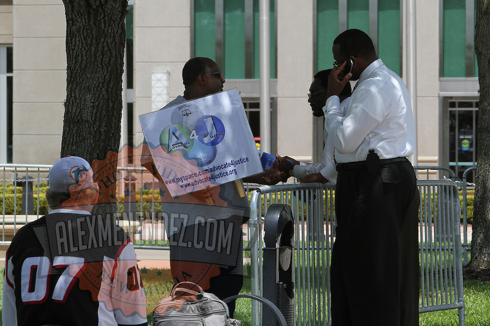 One lone picketer talks in the front courtyard where picketers were expected to rally as George Zimmerman's trial in the shooting death of Trayvon Martin gets underway at the Seminole County Criminal Justice Center on Monday, June 24, 2013 in Sanford, Florida. (AP Photo/Alex Menendez)