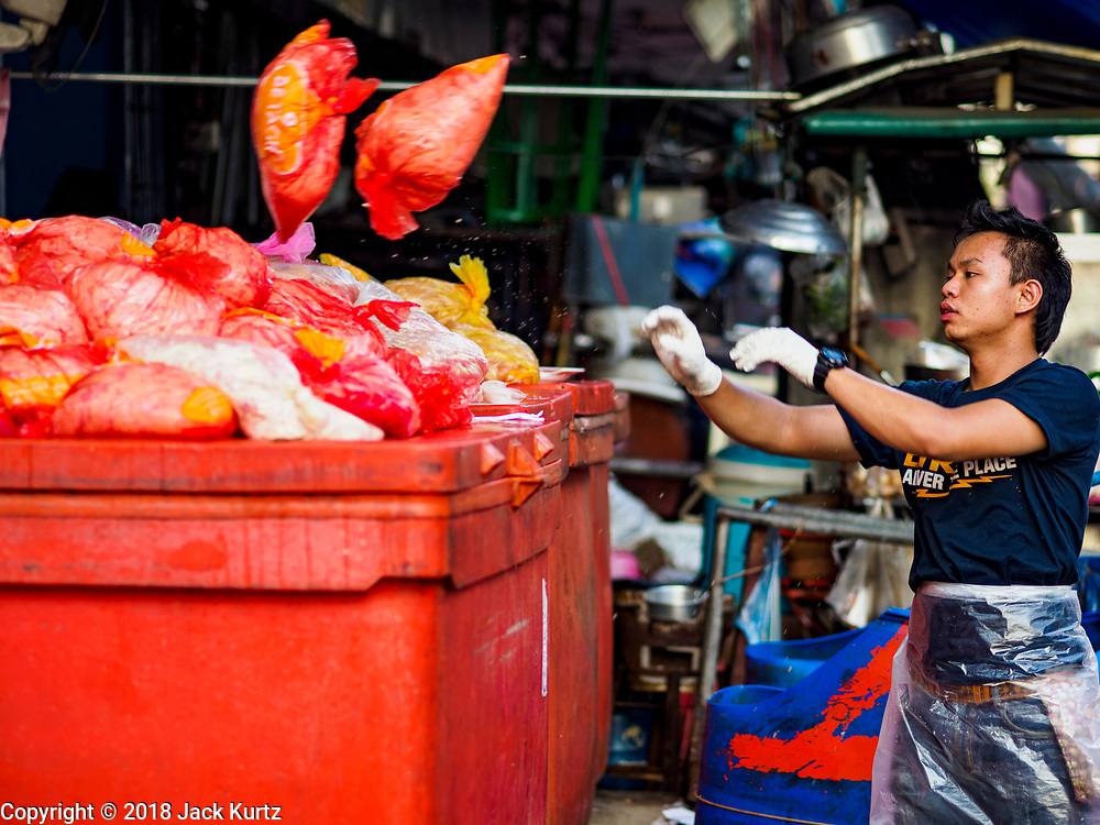 """04 DECEMBER 2018 - BANGKOK, THAILAND:  A worker sorts meat products wrapped in plastic bags in Khlong Toei market. The issue of plastic waste became a public one in early June when a whale in Thai waters died after ingesting 18 pounds of plastic. In a recent report, Ocean Conservancy claimed that Thailand, China, Indonesia, the Philippines, and Vietnam were responsible for as much as 60 percent of the plastic waste in the world's oceans. Khlong Toey (also called Khlong Toei) Market is one of the largest """"wet markets"""" in Thailand. December 4 was supposed to be a plastic free day in Bangkok but many market venders continued to use plastic.    PHOTO BY JACK KURTZ"""