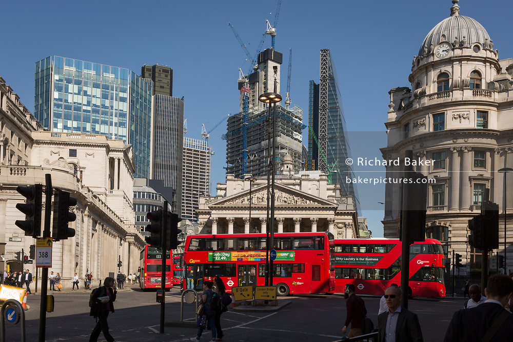 With the Bank of England on the left and neo-classical columns of Cornhill Exchange beneath new skyscrapers rising above the City of London - the capital's financial district (aka The Square Mile), London buses pass through Bank Triangle with on 19th April 2018, in London, England.