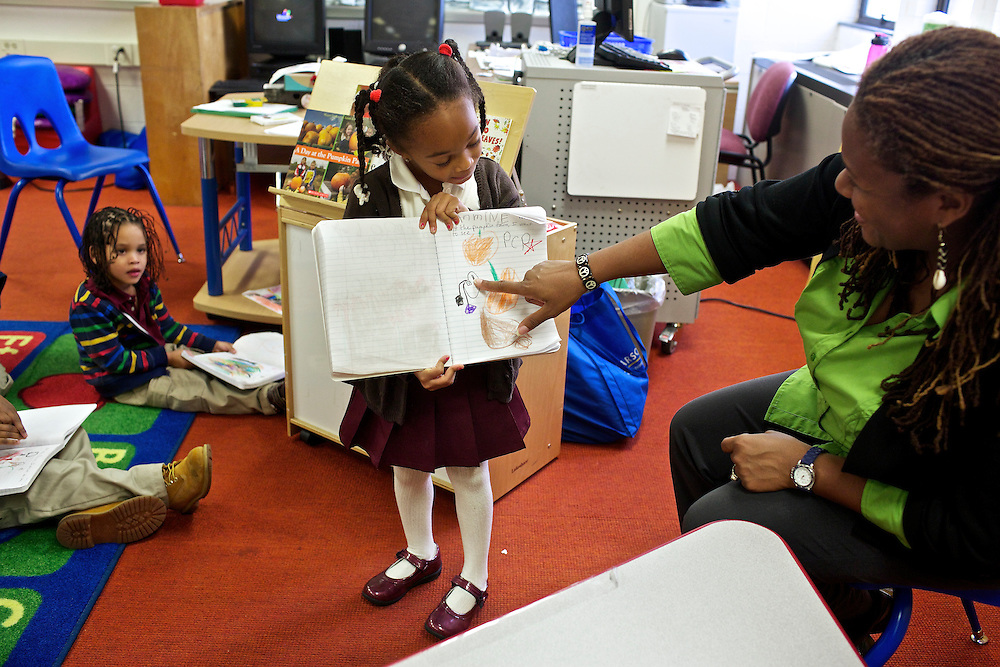 "Calvin Rodwell Elementary School Pre-kindergarten student Jasmine Blanding, 4, shows teacher Erika Parker, right, and the class what she wrote in her journal after students read the book ""A Day at the Pumpkin Patch,"" a non-fiction children's book about visiting a farm. The book was part of a ""Common Core"" reading and learning unit, which aims to follow up non-fiction reading with learning in the field. The day after the children read the book about the farm, they visited Summers Farm in Frederick, MD."