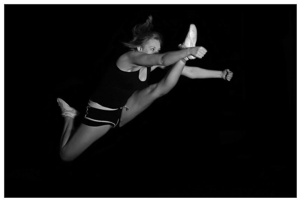 Excellent left leg cheerleading herky jump in black and white.