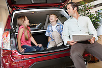 Children with their father sitting in the car