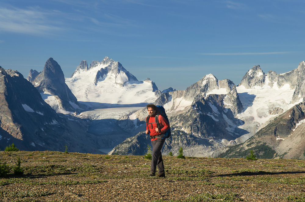 Adult male backpacker on Rocky Point Ridge. Howser Towers, Vowell Glacier, and Northern Bugaboos in the distance. Bugaboo Provincial Park Purcell Mountains British Columbia.