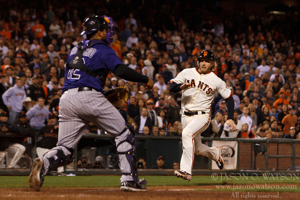 Sep 26, 2011; San Francisco, CA, USA;  San Francisco Giants shortstop Mike Fontenot (14) runs past Colorado Rockies catcher Wilin Rosario (12) to score a run during the eighth inning at AT&T Park.