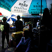 LHASA, JUNE-16, 2009 : a Tibetan trader waits for customers while soldiers guard the street.