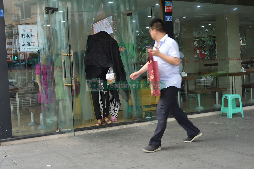 July 20, 2017 - Chengdu, Chengdu, China - Chengdu, CHINA-July 20 2017: (EDITORIAL USE ONLY. CHINA OUT) Zhang Mingshuai, a 26-year-old food deliveryman, delivers food in black mantle in Chengdu, southwest China's Sichuan Province, July 20th, 2017. Zhang wears black bamboo hat and mantle in order to cover his face and not to scare customers because he was badly handicapped at an accident when he was 6 months old. (Credit Image: © SIPA Asia via ZUMA Wire)