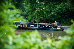 A canal barge leaving the lower basin at Foxton Locks on the Grand Union Canal, Leicestershire, England, UK.