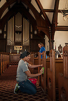 Up With People cast members Alan Slucki of Mexico and Diane Goldsmith of Texas wash down the pews at the Congregational Church Wednesday morning.  (Karen Bobotas/for the Laconia Daily Sun)