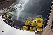 Many penalty charge notices (PCNs) accumulated under the windscreen wiper of a badly-parked car in Brixton, Lambeth, south London.