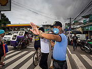 24 JANUARY 2018 - LIGAO, ALBAY, PHILIPPINES: A police officer with a breathing filter directs traffic in Ligao during a volcanic ash fall . The Mayon volcano continued to erupt Tuesday night and Wednesday forcing the Albay provincial government to order more evacuations. By Wednesday evening (Philippine time) more than 60,000 people had been evacuated from communities around the volcano to shelters outside of the 8 kilometer danger zone. Additionally, ash falls continued to disrupt life beyond the danger zones. Several airports in the region, including the airport in Legazpi, the busiest airport in the region, are closed indefinitely because of the amount of ash the volcano has thrown into the air.   PHOTO BY JACK KURTZ