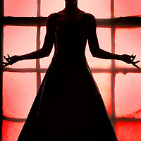 A silhouette of a young lady standing