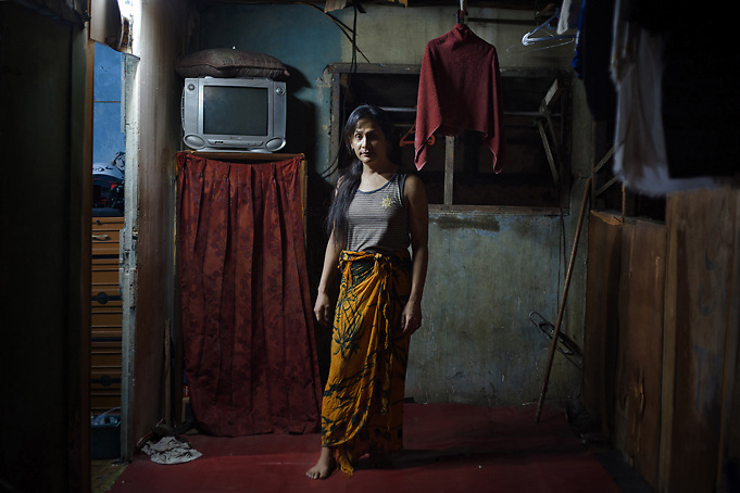 JAKARTA, INDONESIA, MARCH 2013: Ajurn, 32, outside his room at Mami Joyce's house for transgenders, downtown Jakarta.<br /> Traditionally a target of harassment and intimidation in the world&rsquo;s most-populous Muslim country, transgenders in Indonesia - also called 'waria', a term that combines the Indonesian for woman (wanita) and the word for man (pria) - have lately been fighting for better acceptance, thanks to the work of some trail-blazing activists who have themselves endured decades of hardship. <br /> After seeing many colleagues fall victim to AIDS and other fatal diseases, &ldquo;Mami&rdquo; Joyce now takes care of 20 young transgender sex workers living with her as if in a big family. &ldquo;Mami&rdquo; Yuli, a prominent human rights campaigner, has set up a shelter for elderly transgenders, partly funded by a network of churches and a government that until two years ago still deemed them &ldquo;mentally ill&rdquo;. <br /> Also thanks to their efforts, there are signs that the future is getting brighter for this marginalized community, which activists estimate to be at least 3 million-strong in Indonesia. But much still needs to be done, and the threats by recently-emboldened Islamic radicals show that any step towards more tolerance can meet fierce resistance.