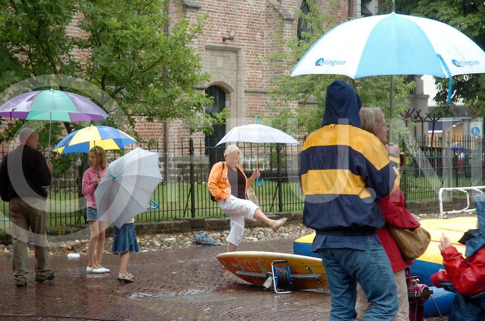060802, ommen, ned<br /> Bissinghdag verregend.<br /> foto: op het Kerkplein werden de niet gebruikte atracties voor de kinderen vanonder de paraplu's bekeken.<br /> De windsurfplank moest het ontgelden.<br /> fotografie frank uijlenbroek&copy;2006 frank uijlenbroek