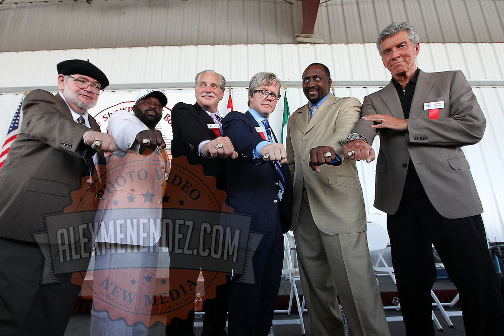 Inductees Michael Katz, Mark Johnson, Al Bernstein, Freddie Roach, Thomas Hearns and Michael Buffer hold their rings out during the 23rd Annual International Boxing Hall of Fame Induction ceremony at the International Boxing Hall of Fame on Sunday, June 10, 2012 in Canastota, NY. (AP Photo/Alex Menendez)