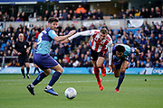 Charlie Wyke of Sunderland heads the ball under pressure from Rolando Aarons of Wycombe Wanderers during the EFL Sky Bet League 1 match between Wycombe Wanderers and Sunderland at Adams Park, High Wycombe, England on 19 October 2019.