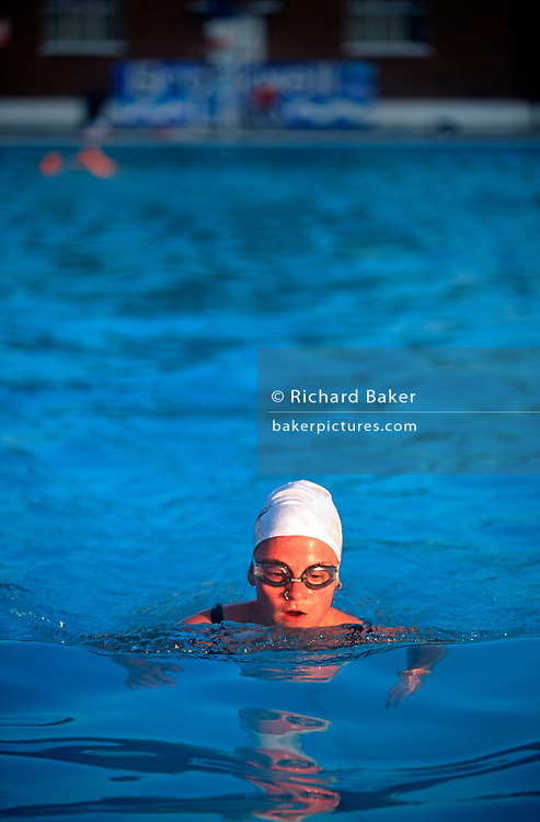An early morning swimmer bathes in the unheated pool of the Grade II listed  Brockwell (Brixton) Lido in Brockwell Park, Herne Hill, 25th August 1995, in London, England. The Lido is an oasis for city dwellers to escape, if only for an hour from the pressures of fast urban life. Brockwell Lido is a large, open air swimming pool in Brockwell Park, Herne Hill, London. It opened in July 1937, closed in 1990 but after a local campaign was re-opened in 1994. Brockwell Lido was designed by HA Rowbotham and TL Smithson of the London County Council's Parks Department to replace Brockwell Park bathing pond. (Photo by Richard Baker / In Pictures via Getty Images)