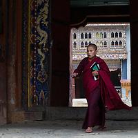 A young monk exits the Gangteng Monastery in Phobjika Valley, Bhutan