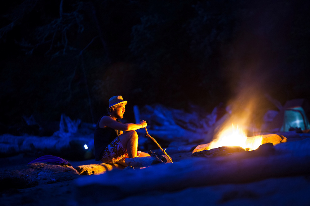 A man sits besides a campfire on the beach at Thrasher Cove, West Coast Trail, British Columbia, Canada.