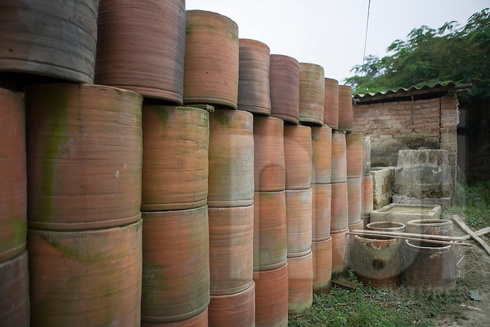 Color film photograph of stacked clay basins in Tho Ha Village, a craft village specialized in making rice paper cakes with a history of pottery ware production, Hanoi outskirts, Vietnam, Southeast Asia