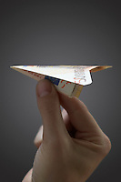Person holding paper airplane made of 50 euro note close-up of hand