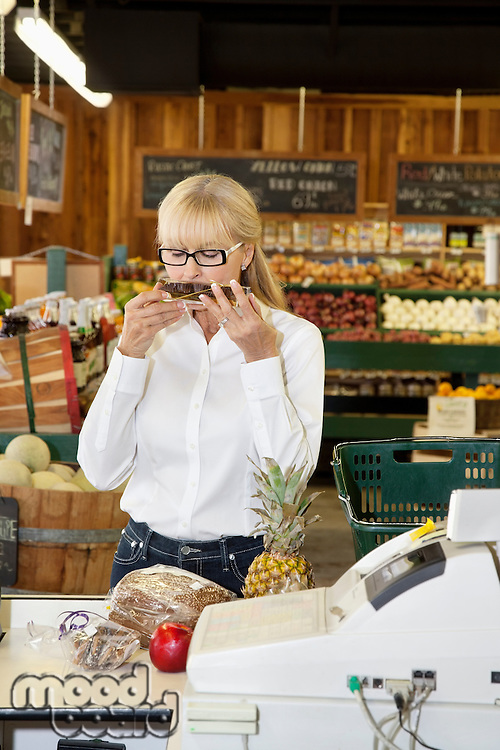 Senior female smelling food at checkout counter