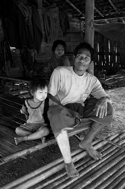 Maung Aye and his daughters in the Lep Per Her camp. <br /> <br /> He lost his leg two years ago after stepping on a landmine on the outskirts of his village, laid by the DKBA (Democratic Karen Buddhist Army, a Karen splinter organisation allied with the Burmese military).  <br /> <br /> Hearing the explosion, his uncle ran to help him, but stepped on another one and was killed.  <br /> <br /> Many landmine victims die from their wounds due to the area's remoteness and the lack of treatment facilities.