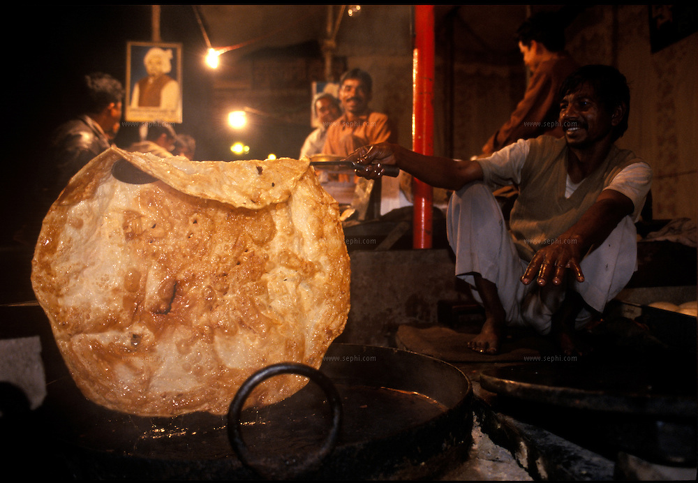 A man prepares a giant Halwa paratha. New Delhi, December 2003