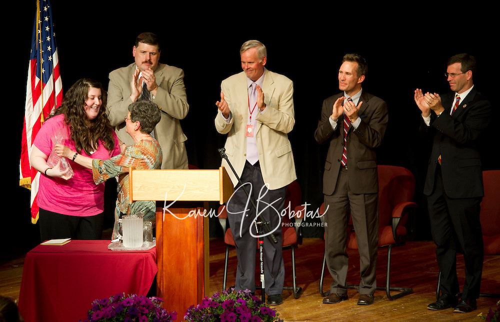 Jennifer Walsh receives an Excellence in Achievement Award along with her diploma from Peggy Selig Adult Education Director during the 40th Annual Laconia Academy Graduation ceremony Friday evening.  On stage to congratulate the graduates are Robert Dassatti Laconia School Board, Robert Champlin Superintendent, Mayor Michael Seymour and Attorney General Michael Delaney.  (Karen Bobotas/for the Laconia Daily Sun)