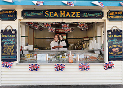 BRIGHTON, UK  29/04/2011. The Royal Wedding of HRH Prince William to Kate Middleton. Across the UK people celebrated the day, even when working. Staff at this traditional fishmongers on Brighton Beach wore masks whilst serving customers. Photo credit should read JULIE EDWARDS/LNP.
